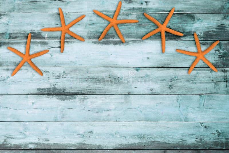 Fem havsstjärnor på turkosträ royaltyfria foton