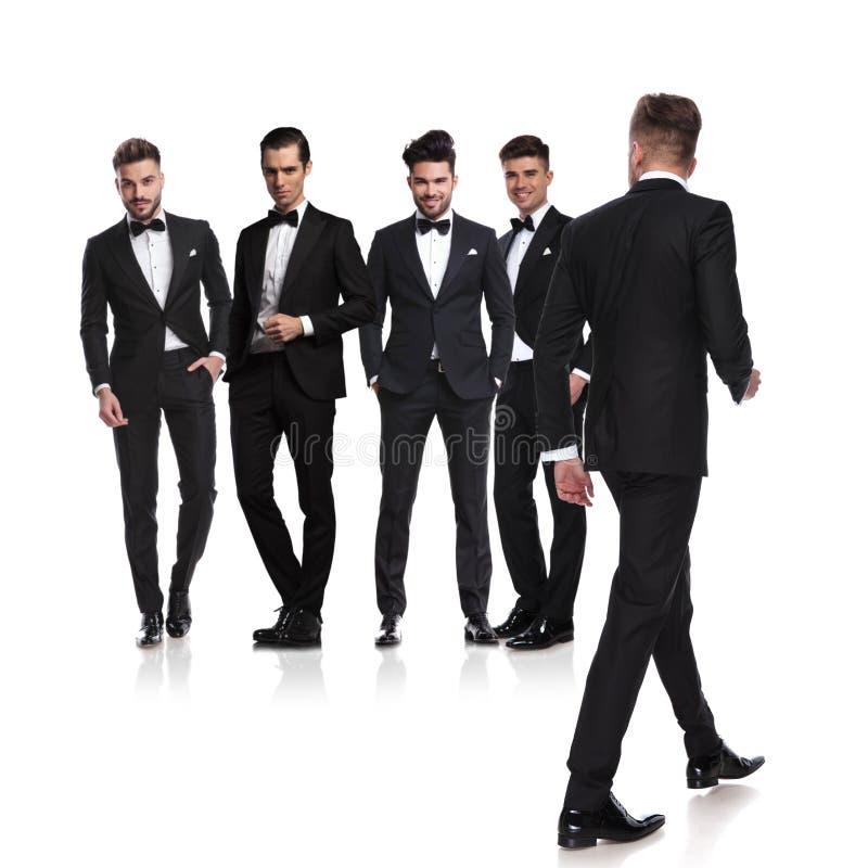 Fem iklädda tuxedoes för män med ledaren som tillbaka går fotografering för bildbyråer