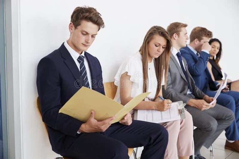 Fem kandidater sitter upp väntande på jobbintervjuer, slut arkivbilder