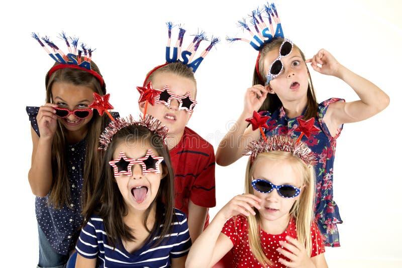 Fem kusiner klädde patriotiskt vara enfaldiga med ett roligt uttryck fotografering för bildbyråer