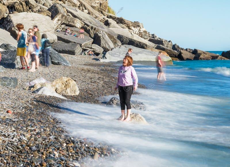 FEM LÄNDER, ITALIEN - APRIL 14, 2013: Folket kopplar av på stranden f arkivbild
