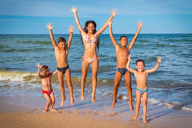 Fem le ungar som hoppar på stranden royaltyfria bilder