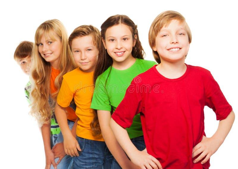Fem lyckliga ungar i färgrika skjortor royaltyfri fotografi