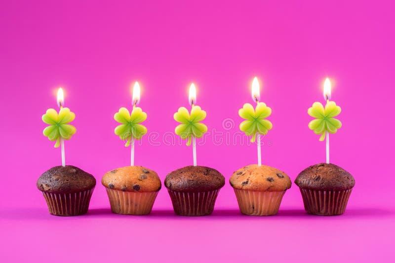 Fem muffin med bränningstearinljus över en rosa bakgrund arkivfoto