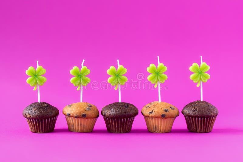 Fem muffin med stearinljus över en rosa bakgrund royaltyfri bild