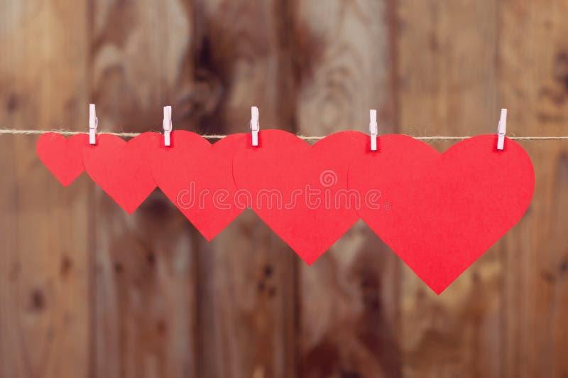 Fem pappers- hjärtor som hänger att stiga arkivfoto