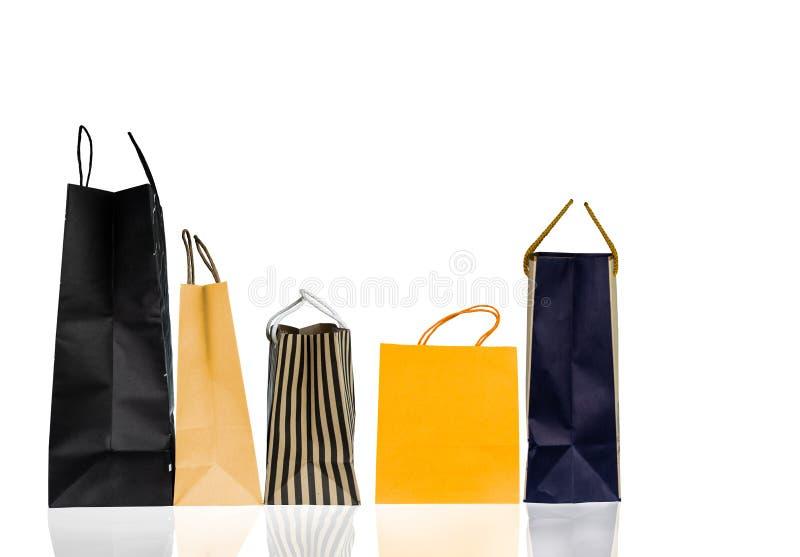 Fem pappers- shoppa påsar som isoleras på vit bakgrund Shoppingpåse med blå, brun och gul färg Rabattförsäljningsbegrepp arkivbilder