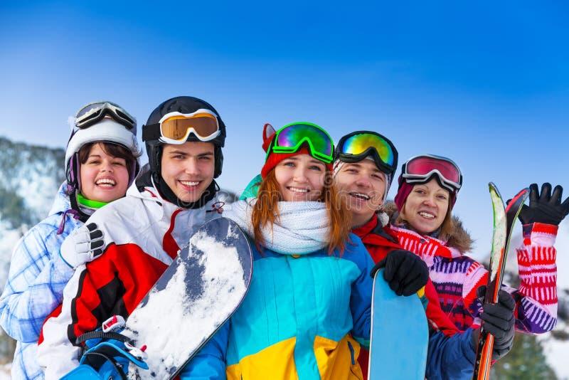 Fem positiva vänner med snowboards arkivbilder