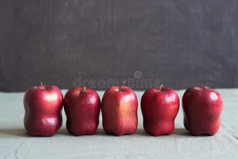 Fem röda äpplen på grungebakgrund royaltyfria foton