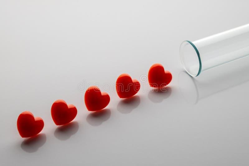 Fem röda hjärtor i rad som droppar av blod från en provrör Det medicinska begreppet av laboratoriumet testar och analyserar kopie royaltyfri fotografi