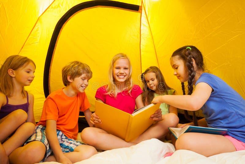 Fem roliga ungar läste boken i ett tält arkivbilder