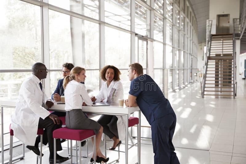 Fem sjukvårdarbetare på en tabell i modernt sjukhus övar påtryckningar royaltyfri foto