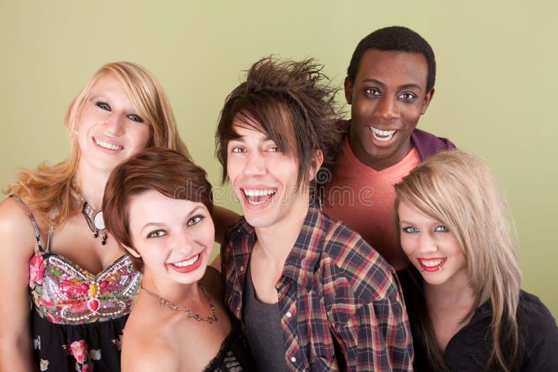 Fem skratta stads- tonår framme av den gröna väggen fotografering för bildbyråer