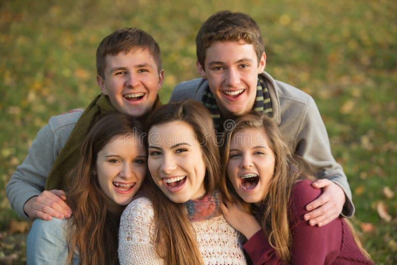 Fem skratta tonår utomhus royaltyfria bilder