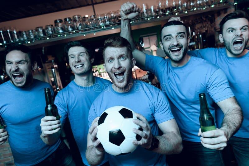 Fem sportfans som dricker öl som framme firar och hurrar av tv på sportstången royaltyfri bild