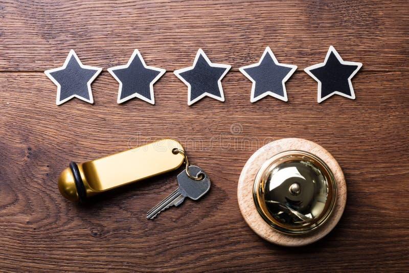 Fem stjärnor, tjänste- Klocka och hotelltangent på träskrivbordet fotografering för bildbyråer