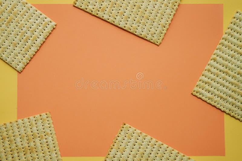 Fem stycken av matzoen på korallen och den gula bakgrunden Tomt avst?nd f?r text Moderiktigt begrepp royaltyfri foto