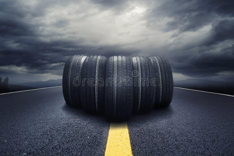 Fem svarta gummihjul som rullar på en väg med moln arkivbild