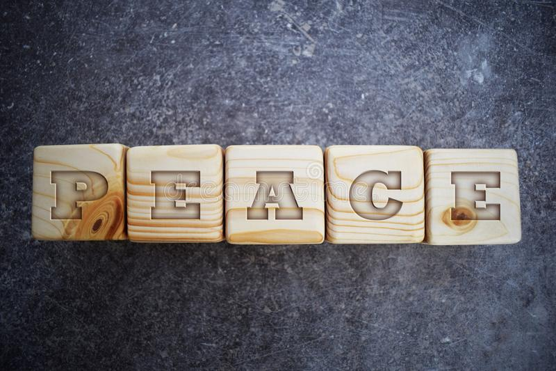 Fem träkvarter med ordet - fred - på grå bakgrund royaltyfri fotografi