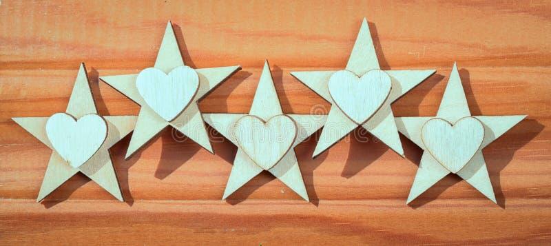 Fem trästjärnor och hjärtor på en träbakgrund arkivbilder