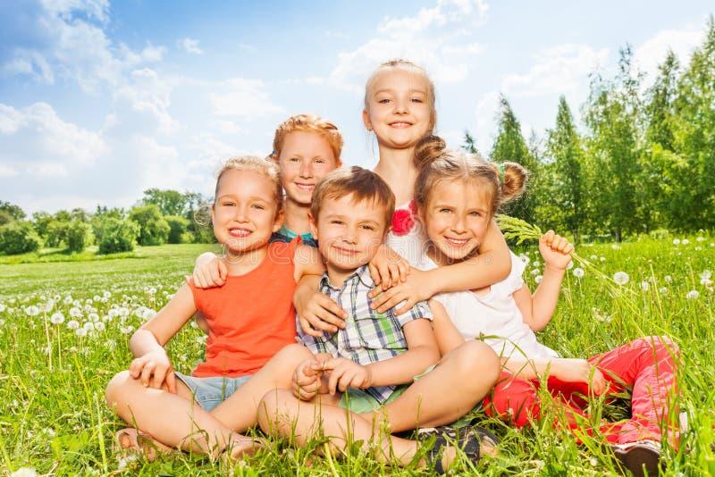 Fem underbara ungar som tillsammans sitter på en äng royaltyfri fotografi