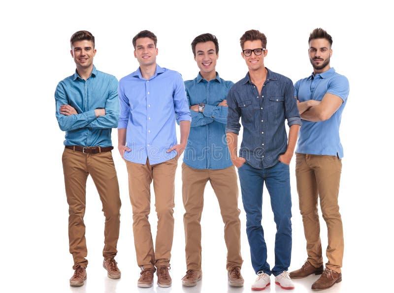Fem unga tillfälliga män som tillsammans står på arbete arkivfoton