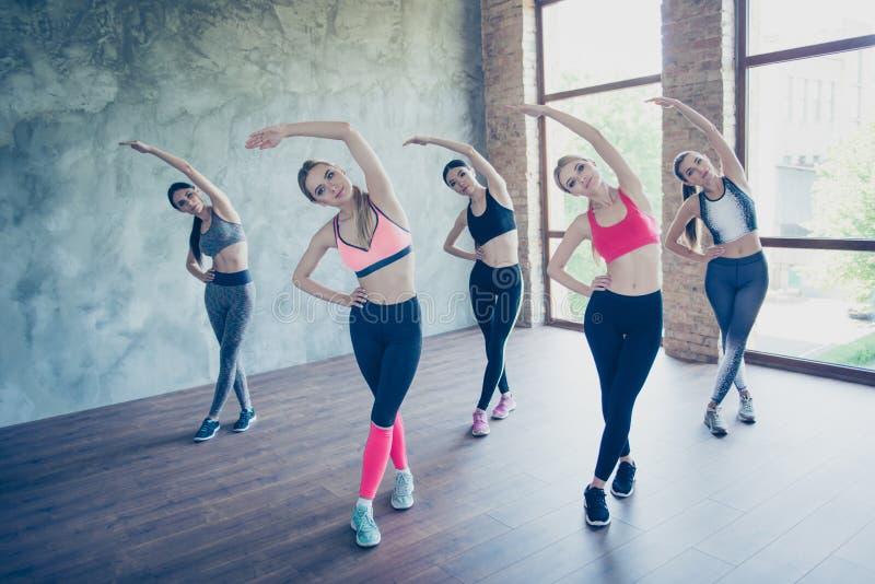 Fem unga trendiga idrottskvinnor är sträckning som, så är bendy och royaltyfria bilder