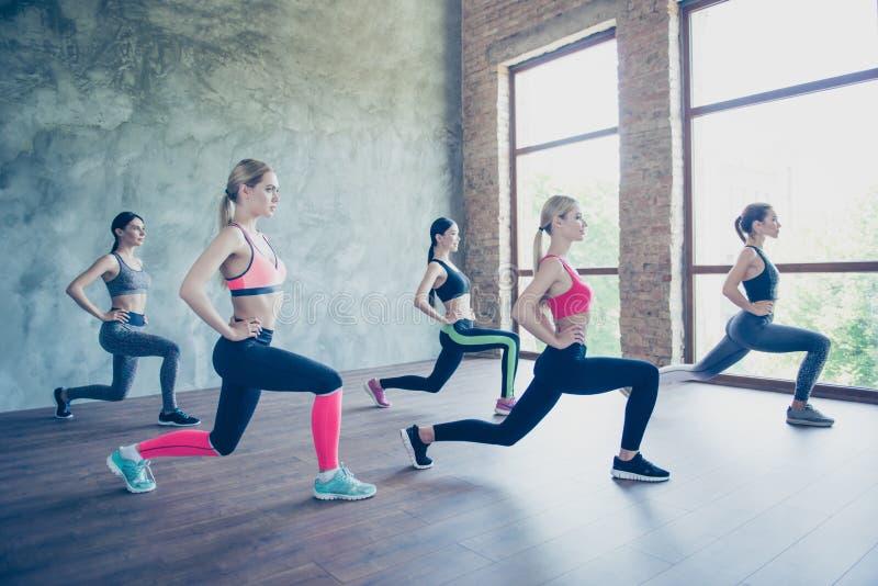 Fem unga trendiga idrottskvinnor sträcker deras ben förbi royaltyfri foto