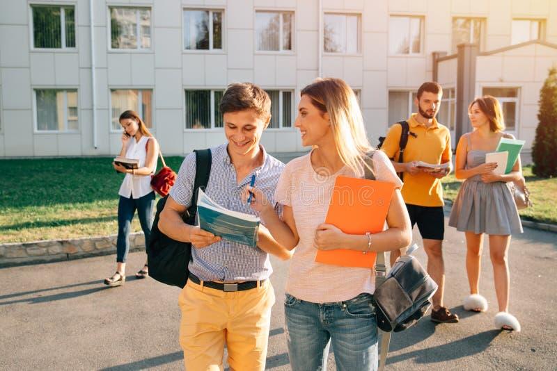 Fem vänliga studenter går, efter de passerade provet utanför högskolabyggnaden och har diskuterat projektet arkivfoton