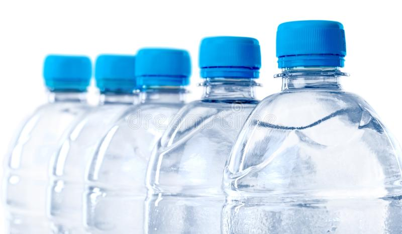 Fem vattenflaskor i rad - isolerat royaltyfria bilder