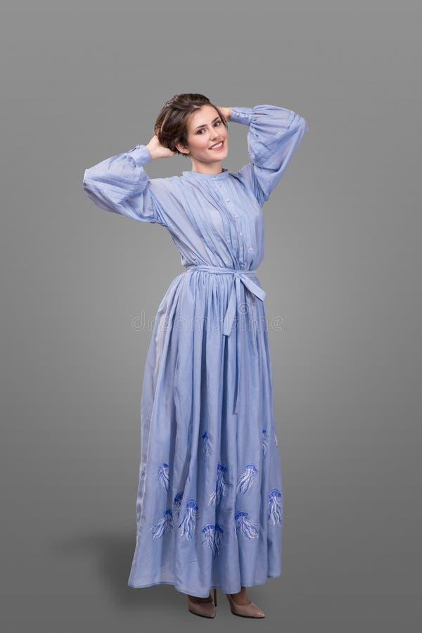 Femail modela odzieży błękita długa suknia nad szarym tłem zdjęcia stock
