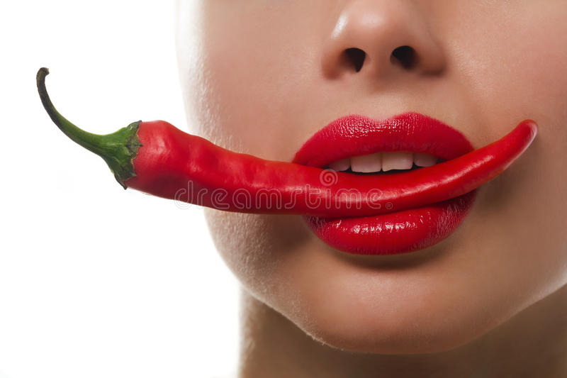 Femail mouth with red hot chilli pepper. Female mouth holding red hot chilli pepper. She has bright red lipstick on her lips royalty free stock photos