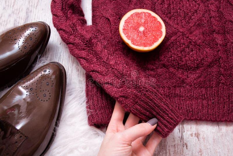 Femaile-Hand, die Kastanienbraun hält, strickte Strickjacke, braune Lackschuhe, Schnittpampelmusenhälften Hölzerner Hintergrund,  lizenzfreie stockfotografie