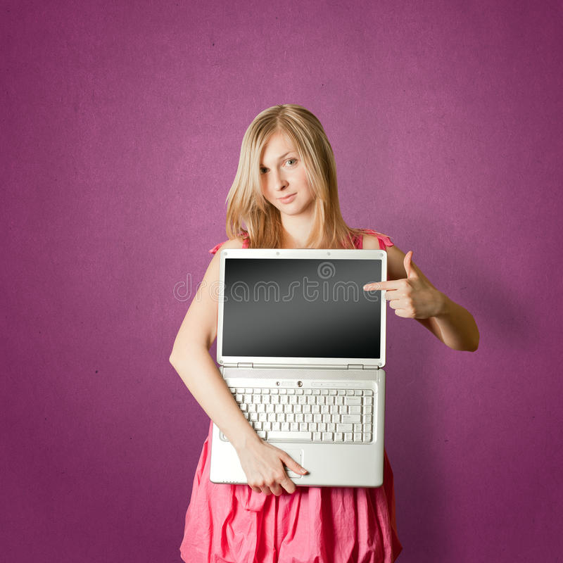 Femaile in pink with open laptop. Femaile woman in pink with open laptop showing something royalty free stock photo