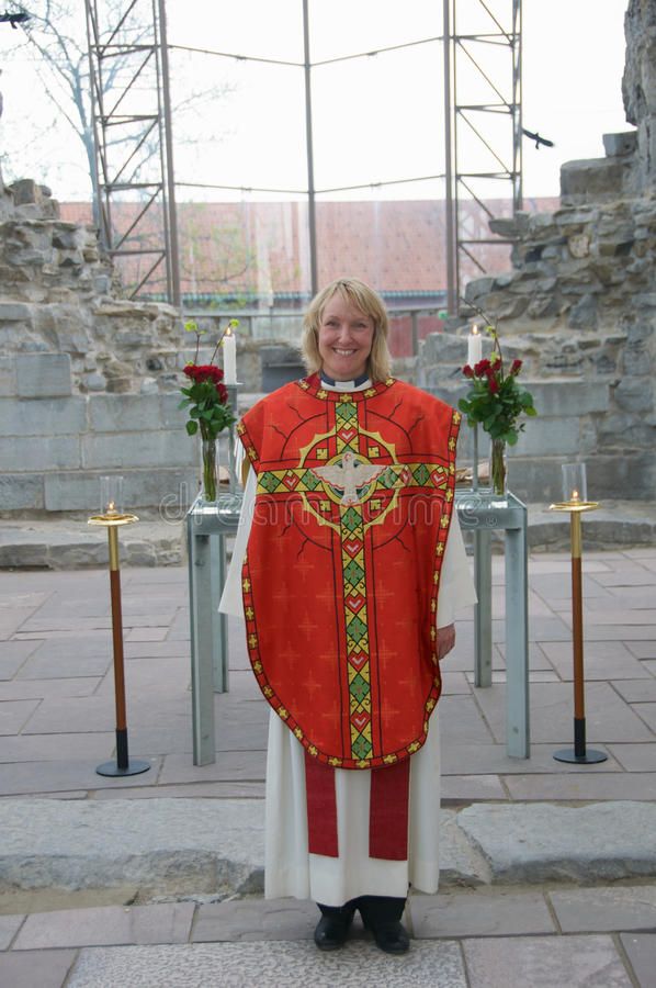 Femal minister in chasuble. Female minister in Church of Norway wearing chasuble for pentacost in the old Dome of Hamar stock photo
