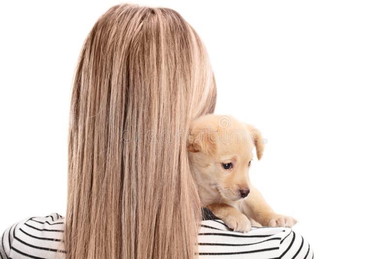 Femal rubio abrazando un pequeño perro de perrito foto de archivo libre de regalías