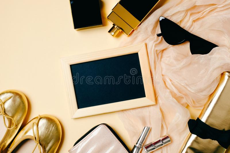 Female accessories set on beige background. Photo frame, sunglasses, golden summer slippers, cosmetic bag, perfume bottle. Womens royalty free stock image