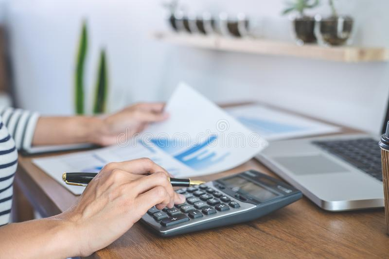 Female accountant calculations, audit and analyzing financial graph data with calculator and laptop Business, Financing,. Accounting, Doing finance, Economy royalty free stock image