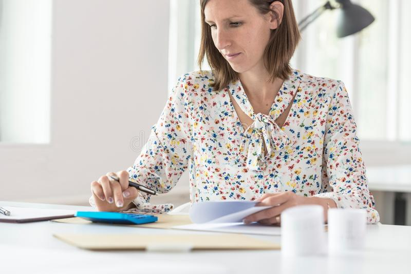Female accountant doing a calculation on a blue manual calculator royalty free stock photography