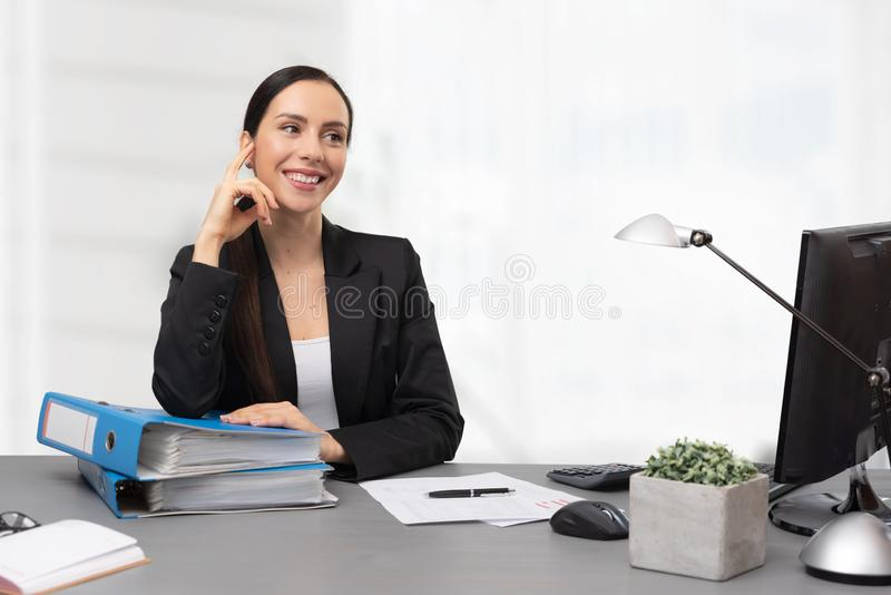 Female accountant sitting at desk in office. Portrait of young smiling bookkeeper stock photo