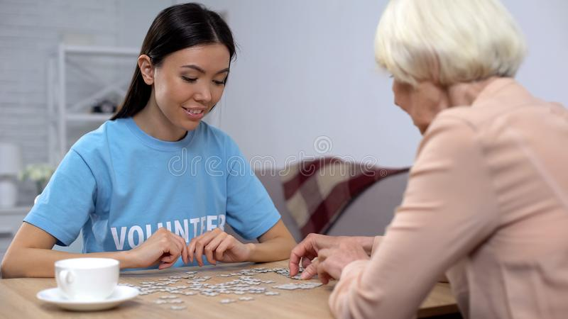 Female activist and senior woman collecting puzzles, Alzheimer disease awareness. Female activist and senior women collecting puzzles, Alzheimer disease stock photography