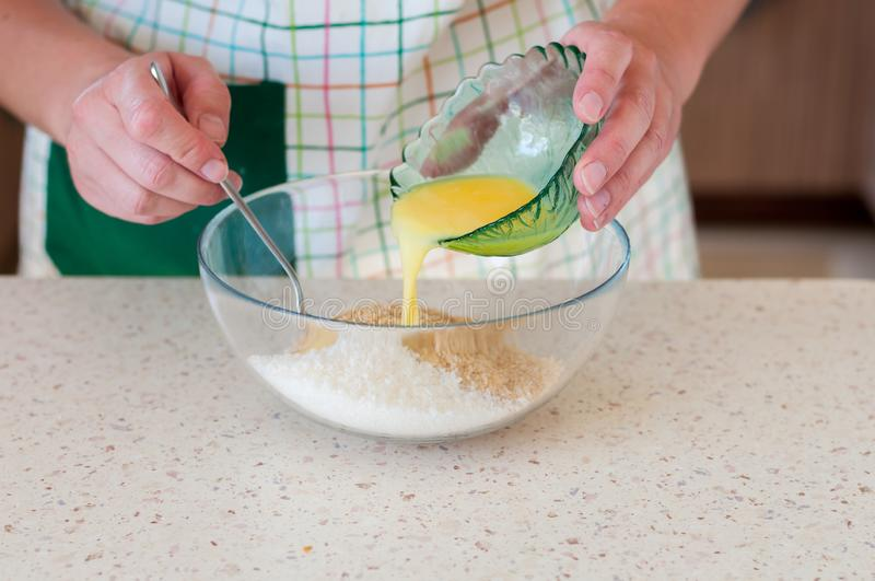Female Adding Butter To Crushed Biscuits stock photo