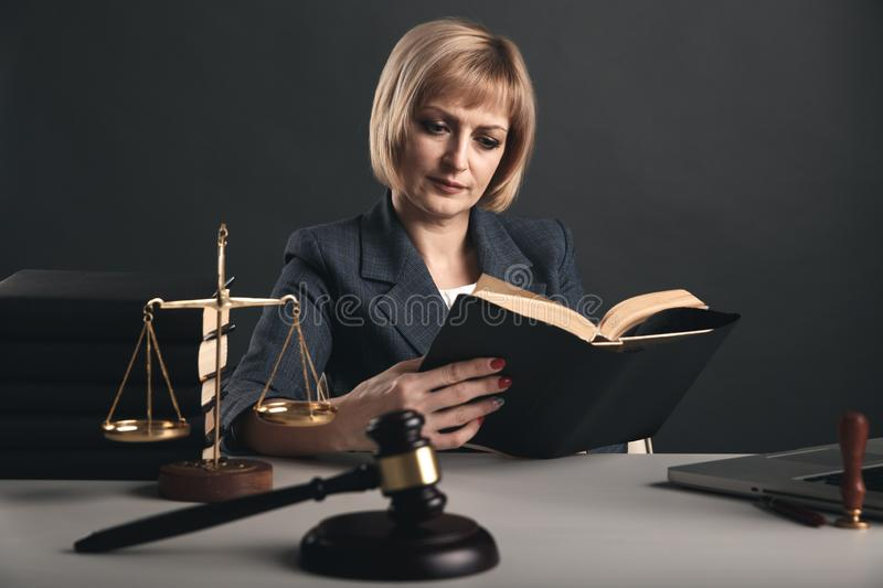 Female advocate with juridical books at her workplace. Gavel and libra on the desk. Female advocate with juridical books at her workplace. Gavel and libra on stock image