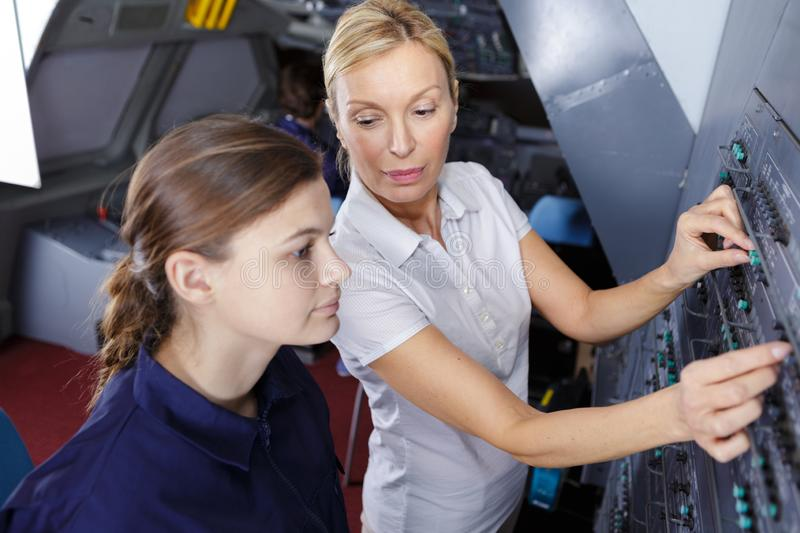 Female aero engineer working on helicopter in hangar. Airplane royalty free stock photos