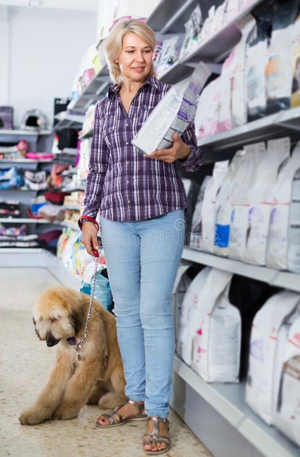 Female with Afghan Shepherd puppy choose pet food in zoo store. Female customer with Afghan Shepherd puppy choose pet food in zoo store royalty free stock images