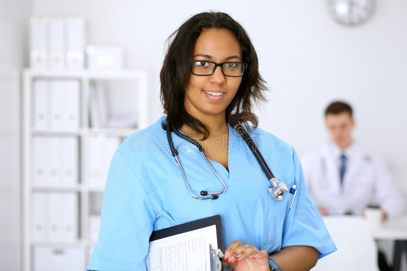 Female african american medical doctor with colleagues in background at hospital. Medicine and health care concept royalty free stock images