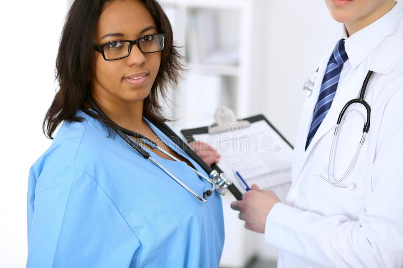 Female african american medical doctor with colleagues in background at hospital. Medicine and health care concept royalty free stock photography