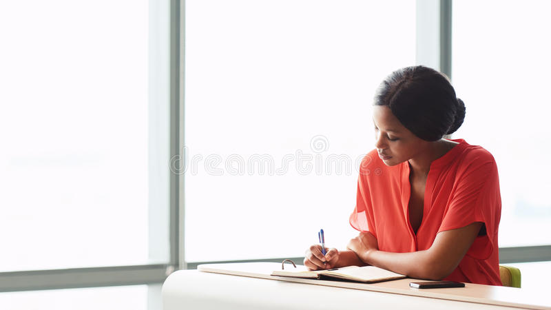 Female African writer busy working while seated next to a window stock images