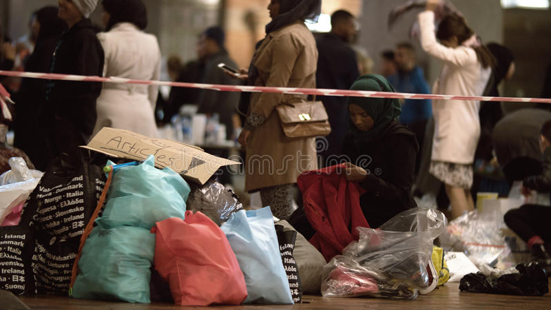 Female Aid Worker Distributing Clothes at Charity royalty free stock photo