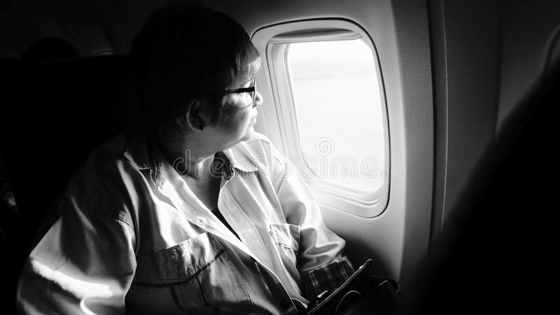 female airplane passanger seeing out of airplane cabin window, black and white high contrast picture style, highlight on woman stock photos